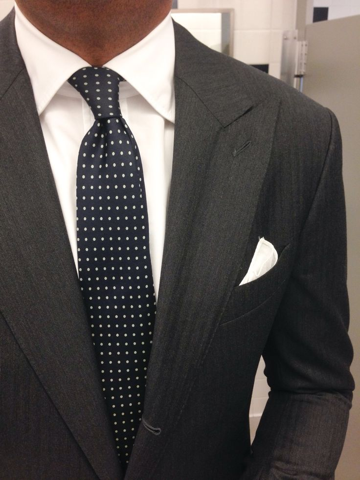Dark grey suit, white shirt, navy tie with white pin dots