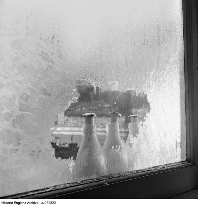 AA072822  Photographer: John Gay.  A row of three milk bottles standing outside a window with frozen milk pushing the caps off, seen through a transparent area scraped in frost on the pane of glass, probably John Gay's house in Highgate.  30-30 Cholmeley Crescent, Highgate, Greater London Authority, N6   Date1960 - 1965
