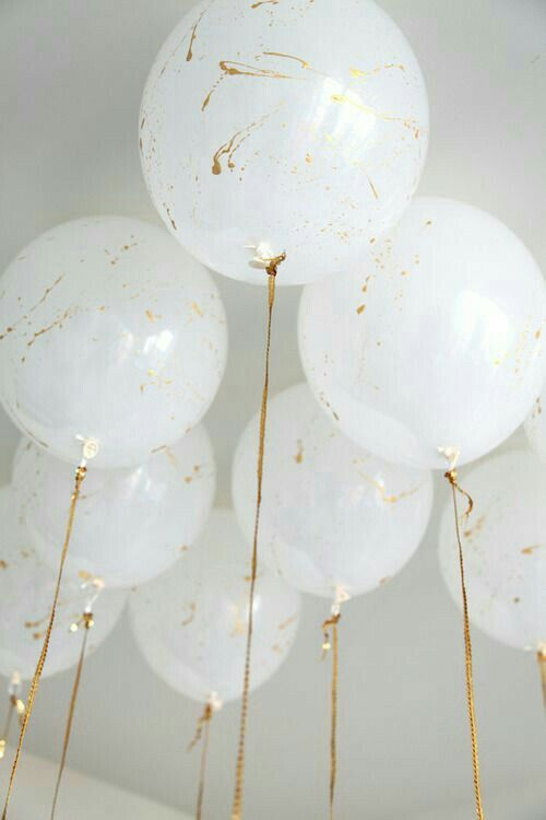 White balloons splattered with gold paint and gold ribbons.