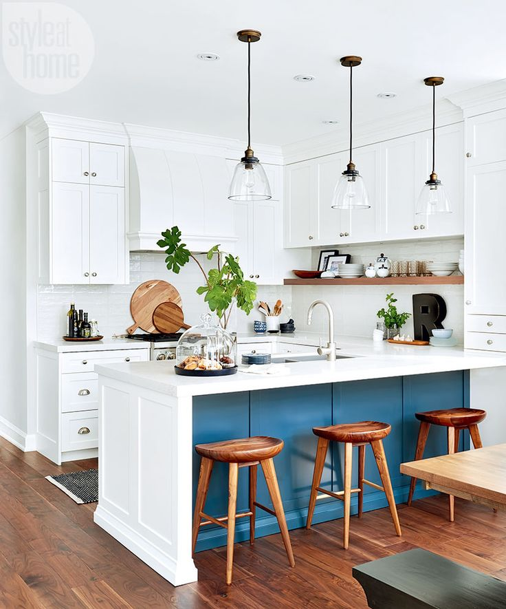 With its crisp white cabinetry, warm walnut accents and quartz countertops, the chic kitchen now boasts a fresh look within the original layout. The bottom of the peninsula – painted rich blue – grounds the room and keeps it from feeling too uniform. Also the blue tone is seen throughout this home.