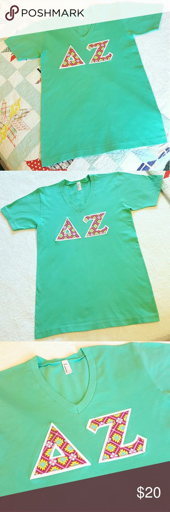 Delta Zeta Sorority Letter T-Shirt ~ Small Beautiful medium teal green, short sleeve, V- neck t-shirt made by American Apparel Co.  Size Small.  100% combed cotton, super soft.  Says Unisex but narrow cut makes it fit more like girl cut!  Standard size Greek Delta Zeta letters in a multi-color geometric/Aztec like print on white backing.  Worn once for about an hour. Basically NWOT.  Perfect condition with no wear, stains, holes or odors.  Freshly laundered and pressed. Ready to wear…