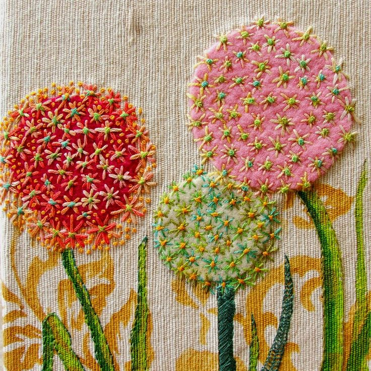 Nice! Looks like appliqué on a printed fabric, worked over with embroidery!