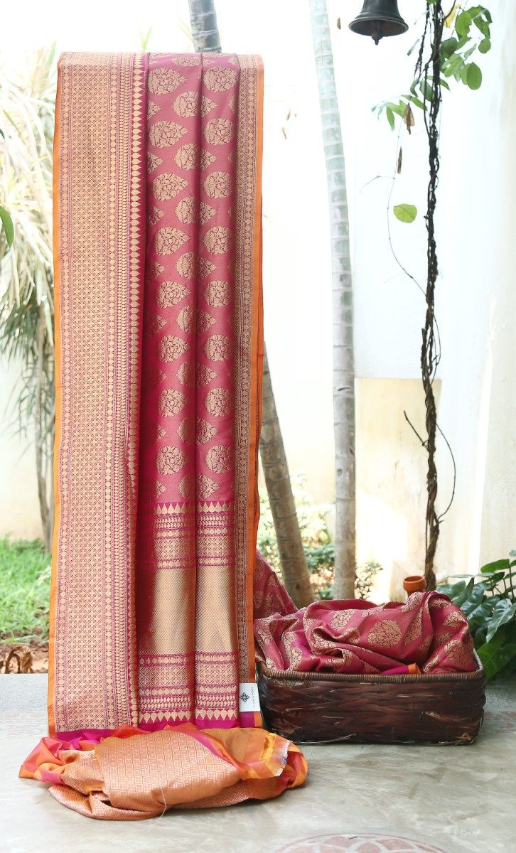 VIBRANT MAGENTA WITH INTRICATELY WOVEN GOLD ZARI BUTTAS ALL OVER HAS DETAILED BORDER AND PALLU. THE ORANGE SELVEDGE AND BROCADE BLOUSE GIVES THE SAREE DAZZLING FINISH.