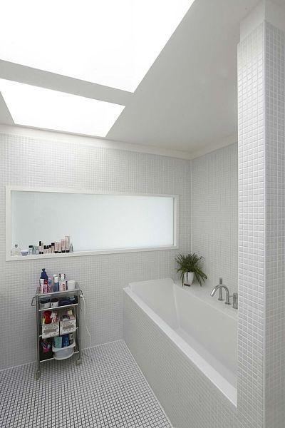 V patře je bílá minimalistická koupelna s čistými liniemi, světlíky a průsvitem přes mléčné sklo ze vstupní haly.