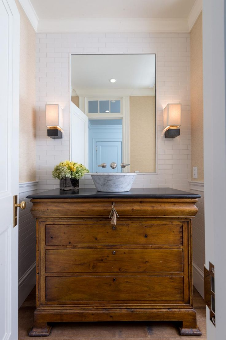 This transitional bathroom blends colors, textures and fixtures to recreate a traditional look in a more contemporary fashion. A chest of drawers serving as counter and storage space, with a Calcutta marble vessel sink and faucet fixtures attached directly to the mirror.