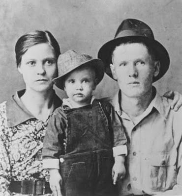 """Elvis Presley with parents, Gladys and Vern. Elvis Aaron Presley (1935-1977) was a twin of Jesse Garon who was stillborn.  One of the most popular American singers of the 20th century.  He is referred to as the """"King of Rock and Roll"""" or simply """"the King"""".  Born in Tupelo, Mississippi, Presley moved to Memphis, Tennessee, with his family at the age of 13. He began his career there in 1954, working with Sun Records owner Sam Phillips, who wanted to bring the sound of African American music to…"""