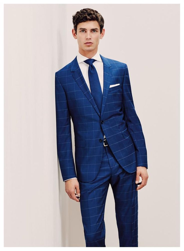 Arthur Gosse dons a blue windowpane suit from Tommy Hilfiger Tailored.