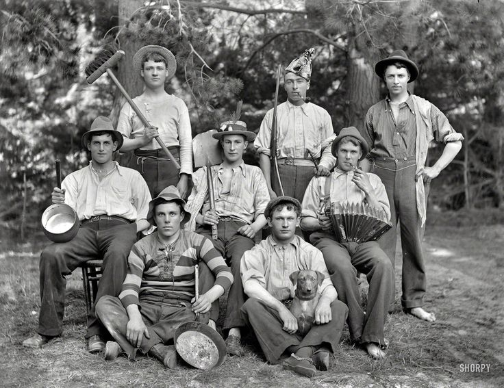 """New Zealand circa 1905. """"Eight young men in ragtag clothing with hats, pots, broom, shovel, accordion, pipes, gun and dog. Sumner, Christchu..."""