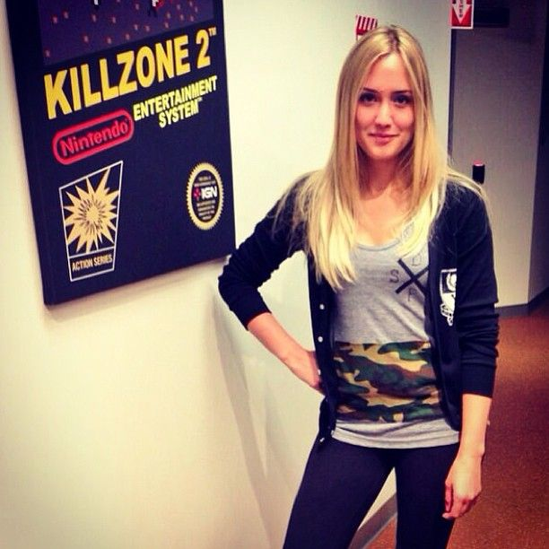 Naomi Kyle from IGN wearing the DFSY camo pocket tank and the Varsity Ghost cardigan