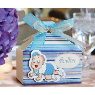 Marturie pentru botez de culoare albastra cu sclipici si dungi, accesorizata cu doua fundite suprapuse albastra, si crem, la care se ataseaza un bebelus.