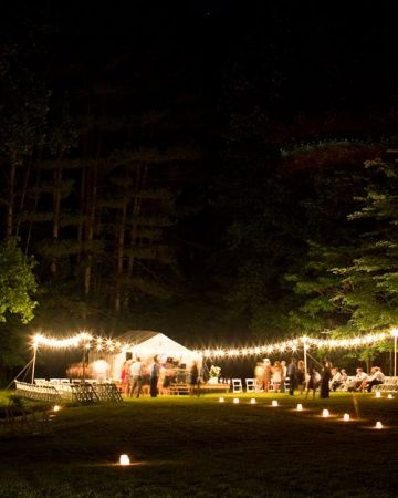 Luminarias (paper bags holding lit candles set in sand) created a glowing path at this eclectic Ohio wedding reception. #receptiondecor #lighting