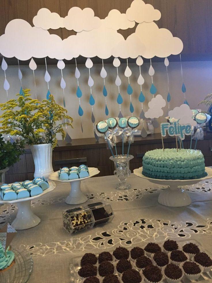 """Chá de bebê para um menino, feito com o tema de nuvens e os dizeres """"está chovendo amor"""". Toda a decoração foi feita em azul e branco, com vários itens personalizados em scrapbook, como o topo de bolo, as sacolas em papel craft, canudos com nuves, mason jars, e suqueiras. O bolo foi feito com degradê de azul e fizemos um painel de nuvem com chuvas em cartolina."""