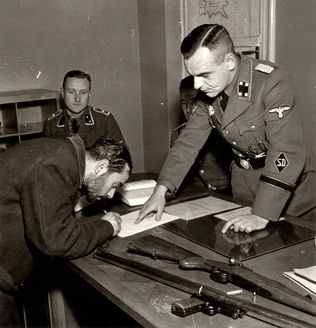 Warsaw, Poland, A Jew who was forced by SD men to sign a confession that he had weapons in his possession.