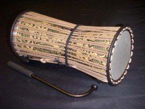 Tambor parlante o tama. Instrumento africano de percusión, mejor que el inglés talking drum. Se trata de un tambor africano occidental con forma de tambor de reloj, cuya altura acústica puede ser regulada para imitar el tono y prosodia del lenguaje humano.