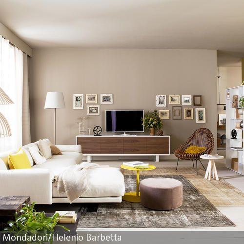 In diesem lichtdurchfluteten Wohnraum bekommt man sofort ein ruhiges Gemüt. Die Wände in Sandtönen wurden mit Vintage-Holzrahmen in der Petersburger Hängung …