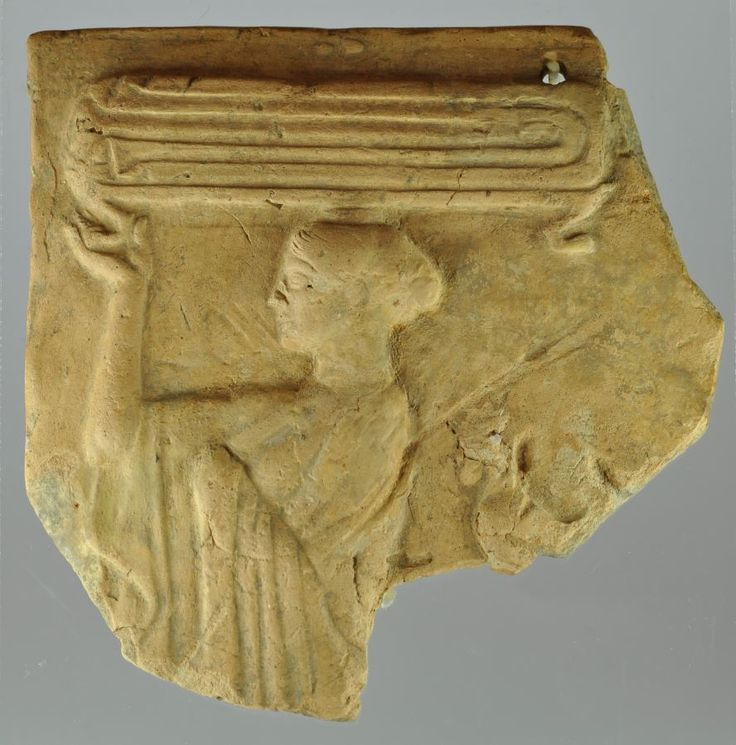 Greek terracotta relief, Locrian pinax, 490-460 B.C. Type 5/6, Greek terracotta relief with woman with himation carrying short legs table over her head, on table a cloth and rooster behind, 14 x 14 cm. Private collection, ex Gorny & Mosch auction 222 26-06-2014 lot 604