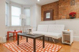 Unverputzte Ziegelwände am oberen Teil der Wandecke und Holzböden machen dieses weiß gestrichene Wohnzimmer.