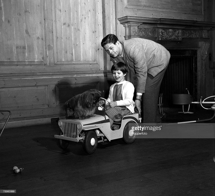 England, 1955, Ex-King Michael of Romania is pictured pushing his eldest daughter Princess Margaret and their pet dog in a toy car