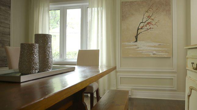 APRÈS : La grande toile qui était originalement au-dessus du buffet a été repositionnée sur le mur et intégrée aux caissons. D'élégants rideaux blancs viennent maintenant habiller la fenêtre, pour une ambiance plus soutenue.