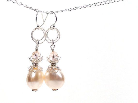 I used the softest peach blush swarovski crystals with creamrose swarovski crystal pearl coins to create this pair of dainty earrings. The color combination is divine, and the silver details add to the romantic intricate look. Materials: Sterling silver and swarovski crystals  Dimensions: Length without ear hook - 1 5/8 inches Length including ear hook - 2 inches  Production time: This item is made to order. The usual production time ranges between 2-10 days. Please see shop announcements…