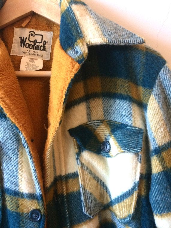 This is a fleece-lined Woolrich wool flannel jacket, with a plaid patten in blue-green, creamy white, and yellow-orange. The body of the interior is lined with a bright orange fleece, and the sleeves are quilted with a thin padding. The jacket features two buttoned breast pockets. This is a super warm and cozy lumberjack style jacket, worn to perfection, perfect for camping or for fall outings. Material: Shell: 85% Wool, 15% Nylon Body Pile Linings: 100% Acrylic Sleeve LIning: 100% Nylon…