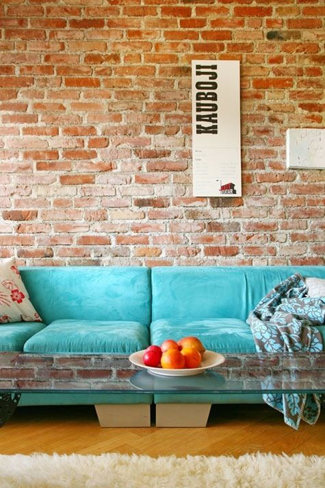 Cyan Velvet Couch--exposed brick wall--glass coffee table with a retro twist--where's my book and coffee!