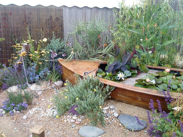beaut beach nautical garden with a boat lily pond and tropical planting at Hampton court garden show - from http://www.gardengoer.blogspot.co.uk/