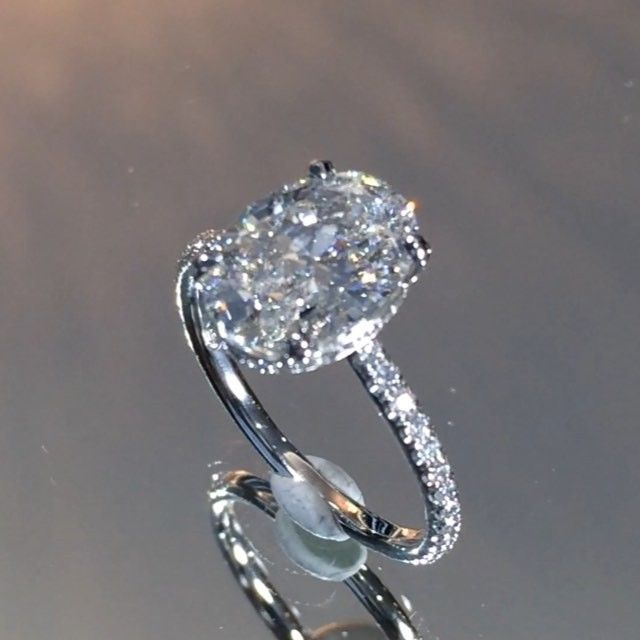 "SWe are predicting this to be THE engagement ring design of 2016.  Shown here with a 2.30 carat #ovaldiamond, this handmade setting features a gently sloping micropave band that leads up to a perfectly fitted wrap of diamonds underneath the center-stone.  The beauty of this ring is the ""invisible gallery"" meaning there is no metal or bar between the bottom of the diamond and your finger.  This gives the ring an ultra airy profile appearance and this ring can be custom ordered"