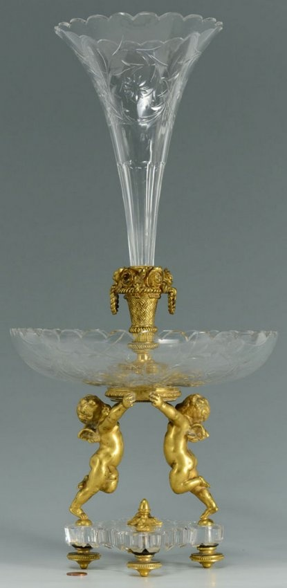 A Baccarat etched crystal and gilt bronze figural epergne featuring two standing cherubs supporting a crystal bowl with a central trumpet vase. Marked Baccarat on the bronze base of the trumpet vase. 19 3/4 total height. 20th century.
