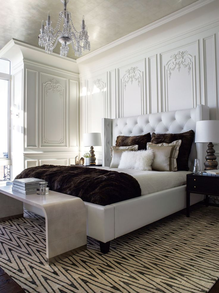 The master bedroom contrasts a modern white leather tufted bed with over-scaled faux fur pillows and throw; decorative painting and antiqued...