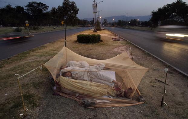 Un uomo dorme su uno spartitraffico a Islamabad, in Pakistan. (Muhammed Muheisen, Ap/Lapresse)