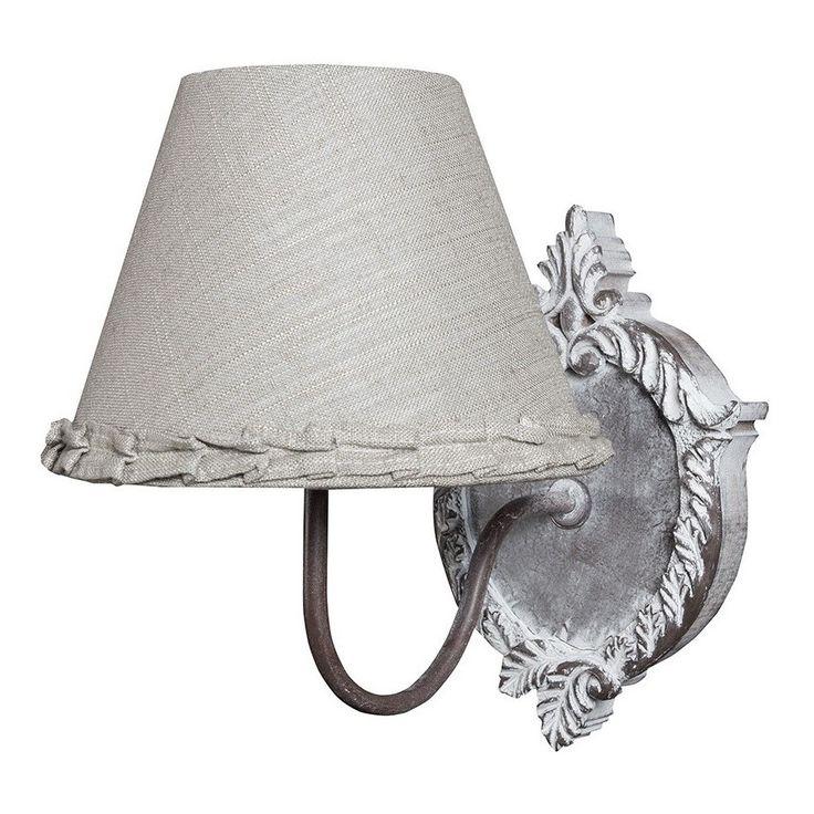 Kinkiet marki Belldeco, posiada abażur obszyty szarym materiałem i pięknie zdobioną podstawą w typowo prowansalskim stylu.