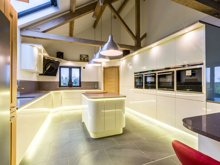 In Line Ivory gloss handle less kitchen by Sheraton featuring Lissa Oak accents, feature lighting, quartz Portobello worktops and a warm coloured splash back.