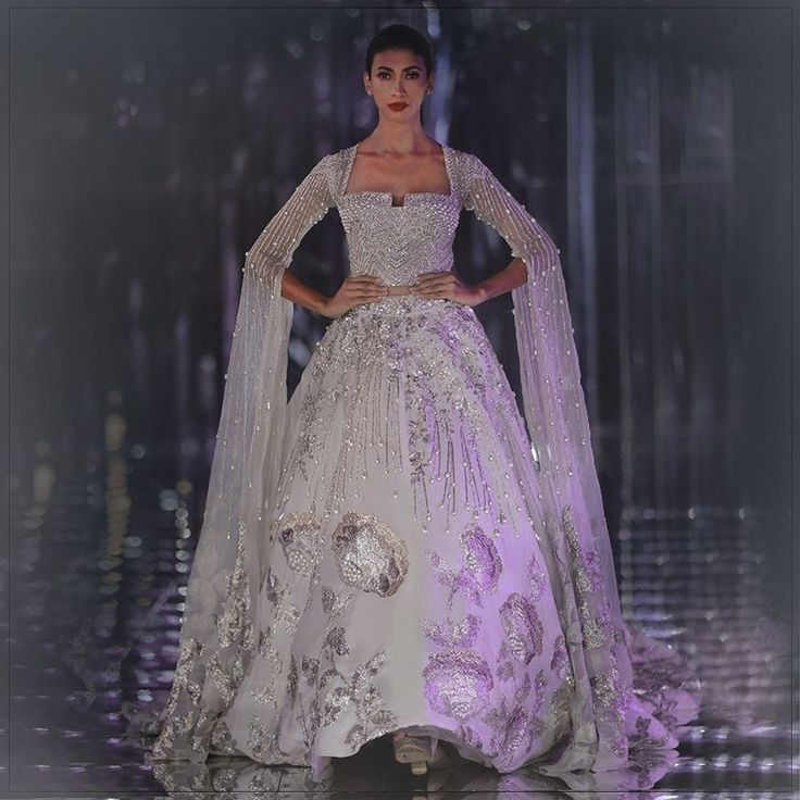 This dreamy couture piece looks magical on the runway with it's delicate neckline & trailing sleeves on a highly embellished corset blouse.