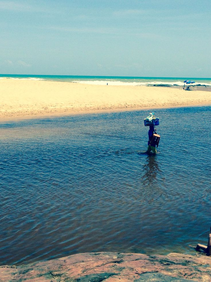 Una mujer cargando sus productos por el agua en Praia del Forte
