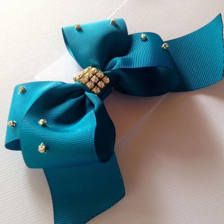 Laço feito em fita tipo gorgorão com aplicação de strass, pode ser colocado no bico de pato na tiara ou na xuxinha de amarrar o cabelo, coloco como o cliente preferir.