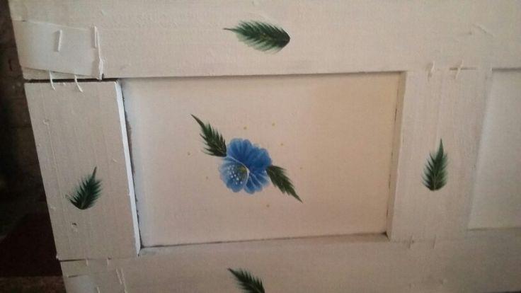 Le realizamos unas flores pinceladas en tonos azules con hojitas verdes...