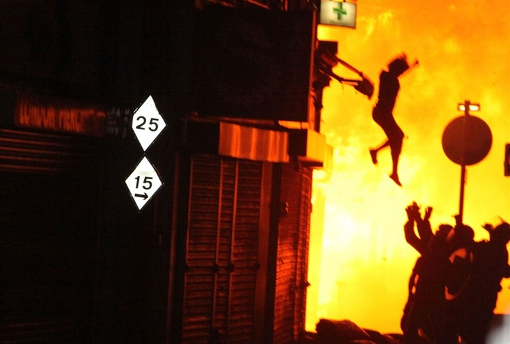 A woman jumps from a burning building in Surrey Street after rioting took place in Croydon, south London, U.K. on Aug. 8.