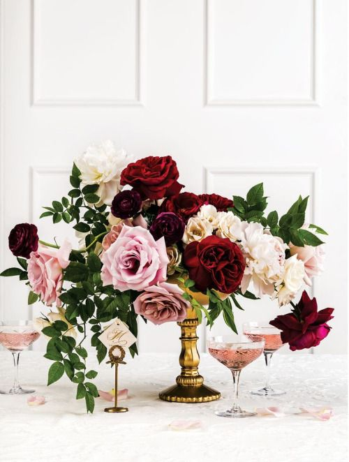 FLORAL CENTERPIECE (Proposal#1): A gold pedestal vase filled with white hydrangea, pink Esperance roses, red freedom roses, pink spray roses, black magic roses, burgundy scabiosa flower and the greenery of silver dollar eucalyptus, nagi, seasonal foliage ad smilax vine surrounded by a trio of assorted gold mercury votives