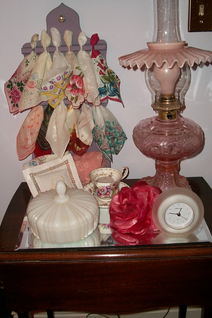 old hankies in painted spoon holder. milk glass bowl, Birthday month cup and saucer, pink glass lamp with pink bulb.