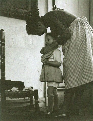 Tasha dressing a child by photographer Nell Dorr