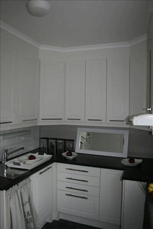 Her er  en liten kjøkkenkrok pyntet med røde epler.  Nettopp satt inn dette kjøkken,så ingen matrett å lage. Helt tomt inne i skapene. Skal fylles før Jul.