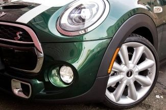 Front corner of 2015 British racing green MINI Cooper S Hardtop with white bonnet strips.
