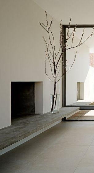 A simple, elegant fireplace with a concrete mantle