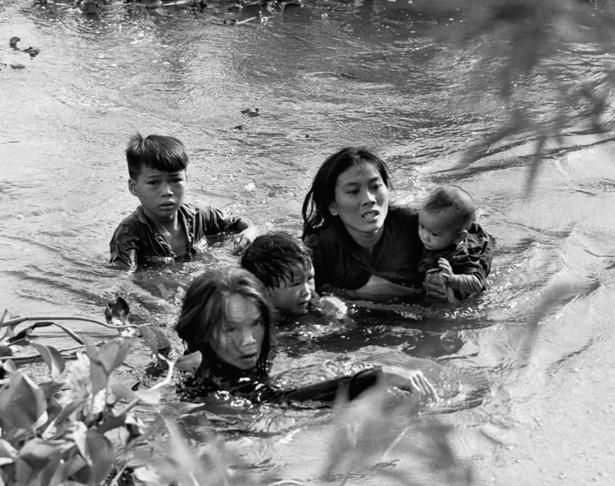 Sept. 7, 1965, a Vietnamese mother and her children wade across a river, fleeing a bombing raid on Qui Nhon by United States aircraft.