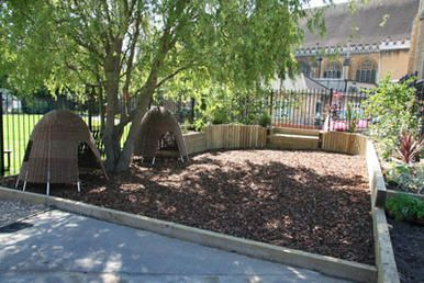Early years outdoor environment, barked area, wicker shelters