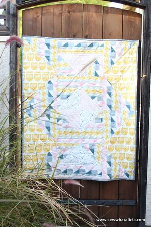 """""""This beautiful quilt was made using the Heartland fabric from Pat Bravo and Art Gallery Fabrics. This quilt was inspired by a Scandinavian prompt. This is a beautiful lap size quilt that is perfect for sitting on the couch or enjoying an outdoor pic"""