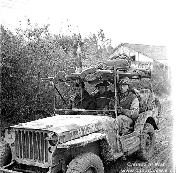 The Moro Valley - A jeep ambulance of the Royal Canadian Army Medical Corps (R.C.A.M.C.) bringing in two wounded Canadian soldiers on the Moro River front south of San Leonardo di Ortona.