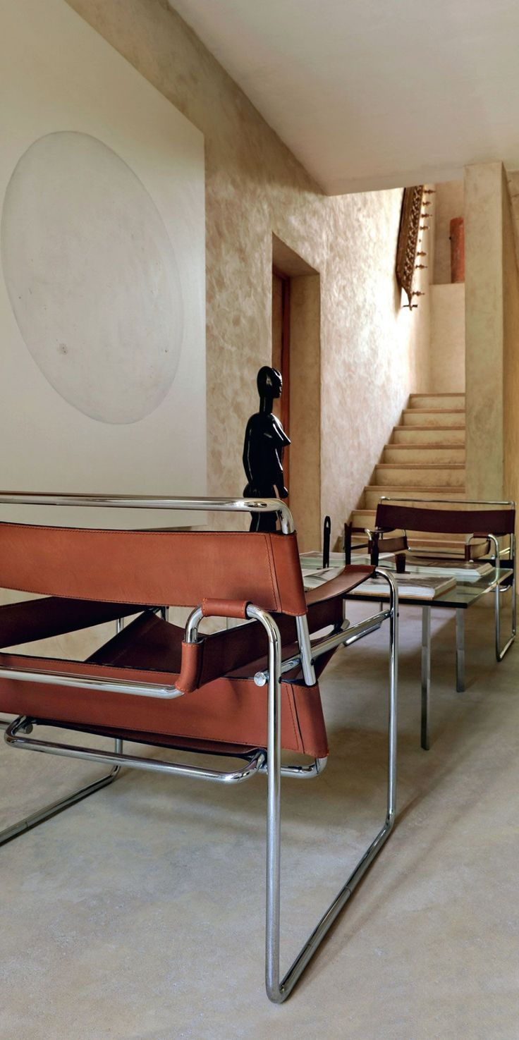 French interior with iconic Bauhaus design: Wassily lounge chairs (model MB3) of tubular metal and leather by Marcel Breuer (1925-1926) and Barcelona low table by Ludwig Mies van der Rohe (1929). / Côté Maison