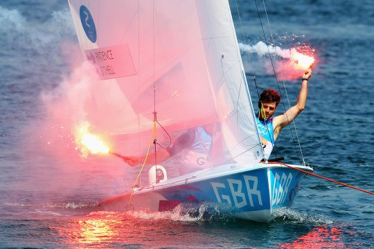 Luke Patience (R) & Stuart Bithell (L) of G.B. let off flares after finishing 2nd, winning the silver medal, Men's 470 Sailing
